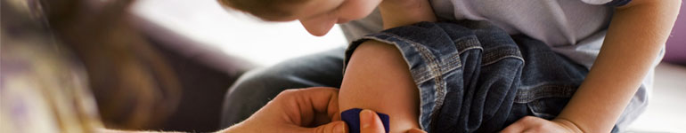 Vendor Directory - Parent putting bandage on child's leg.